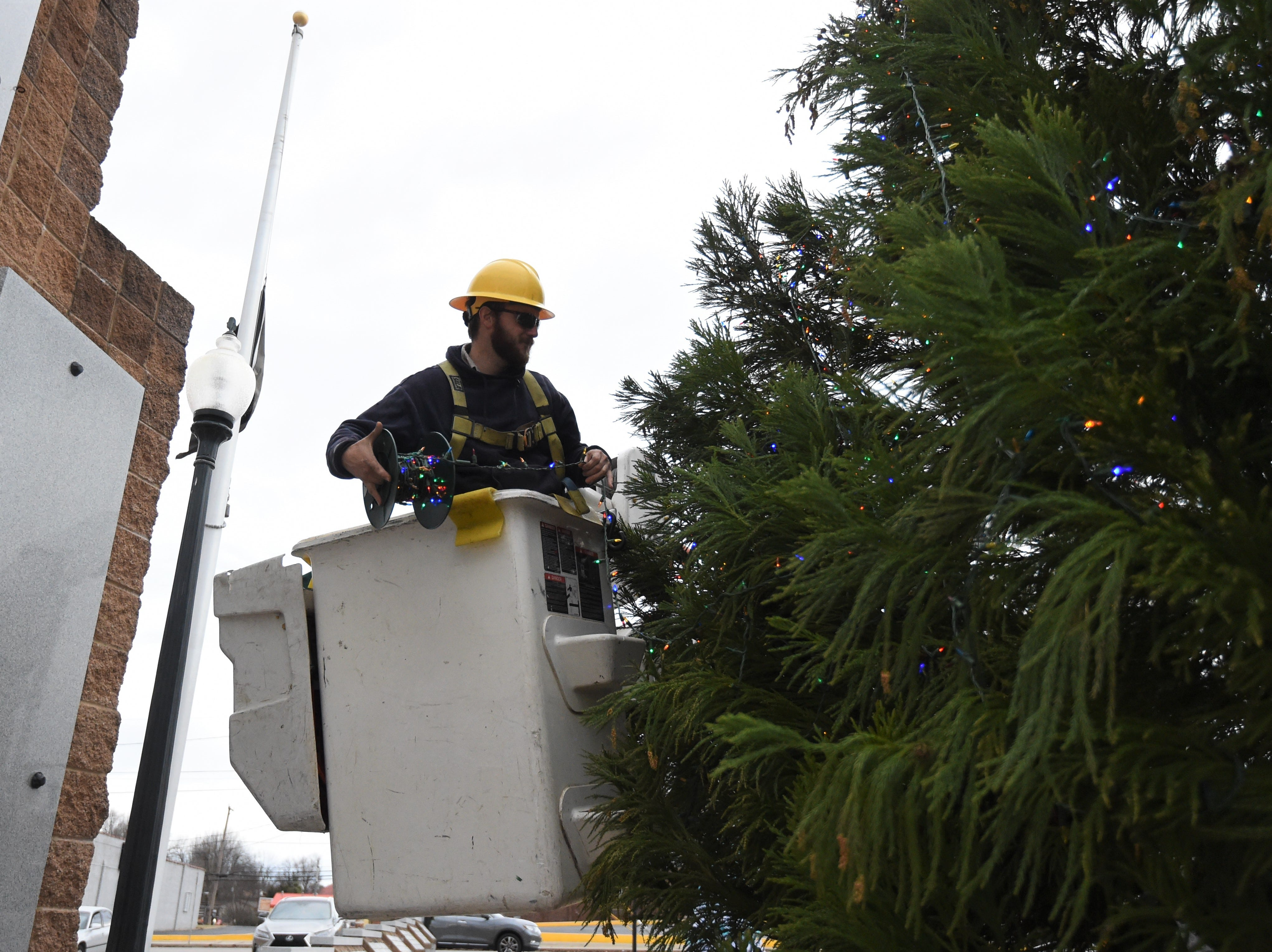 Chance Bailey with the North Arkansas Electric Cooperative uses a bucket truck Thursday to help trim the 30-foot Christmas tree on display at the Veterans Plaza in downtown Mountain Home. The 30-foot tree will make its official debut tonight in the First Security Bank Tree Lighting Ceremony.