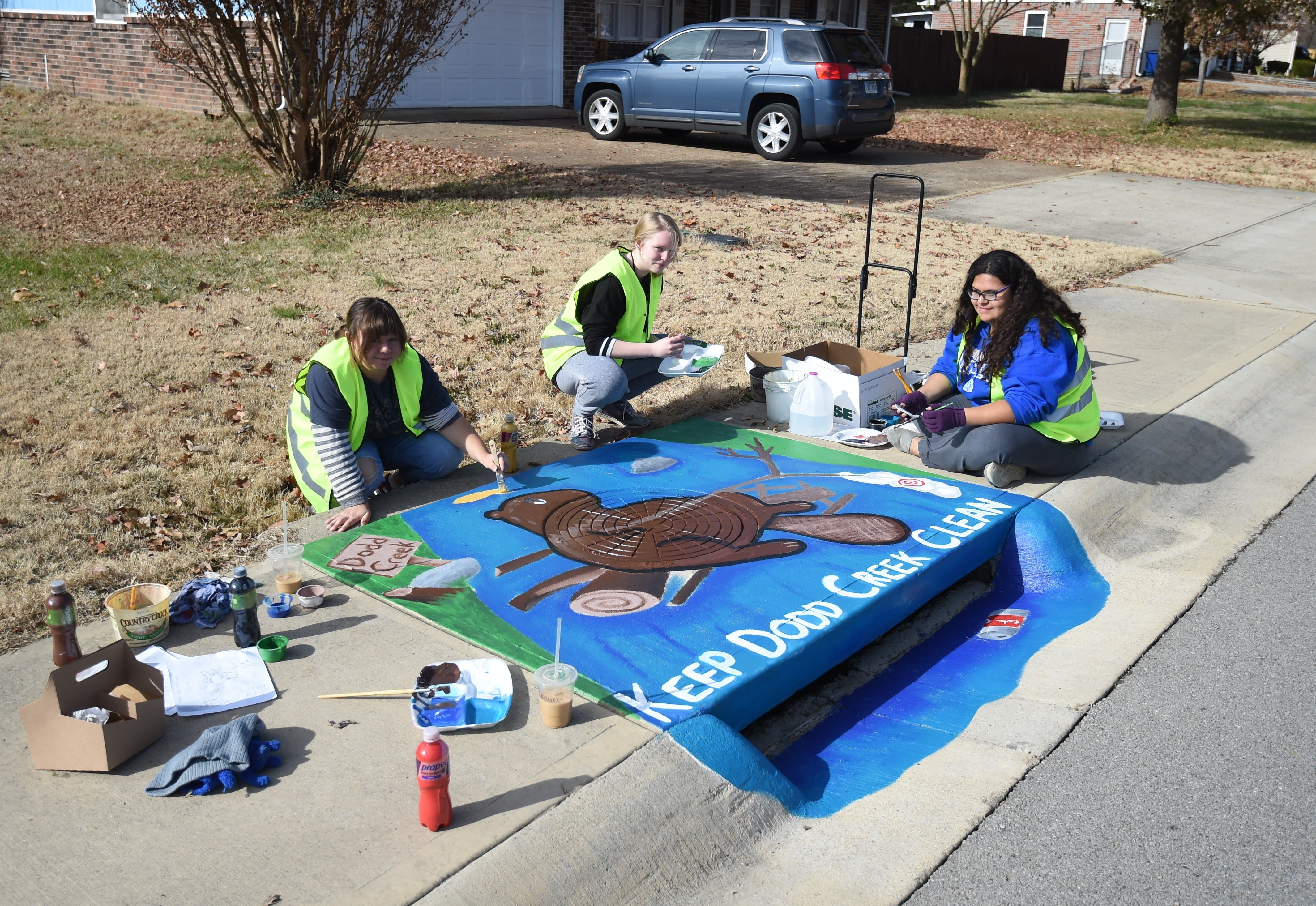 Mountain Home High School students (from left) senior Amberly Schaffer, junior Kaitlyn Miller and senior Saidi Villalvazo work on their storm drain artwork on Nov. 18. The ongoing 'Paint the Drain' program has Mountain Home High School students decorating the stormwater drains along Bomber Boulevard with eco-friendly artwork and messages.