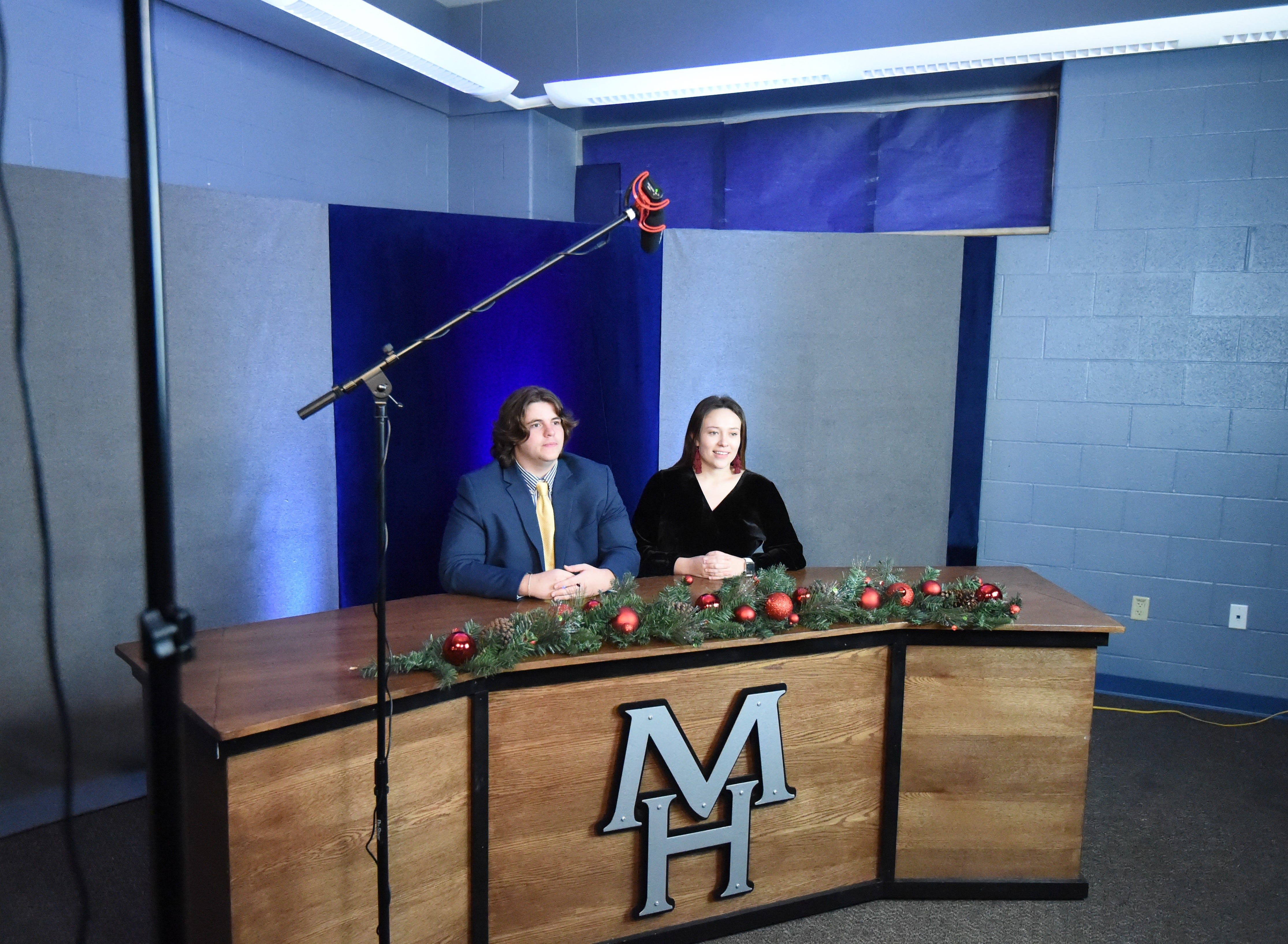 A microphone hangs above the heads of Bomber News Network anchors (from left) Zachary Spaulding and Sophie Quick during Tuesday's recording session. Suspending the mic above the news desk was a new wrinkle for the Dec. 13 broadcast.